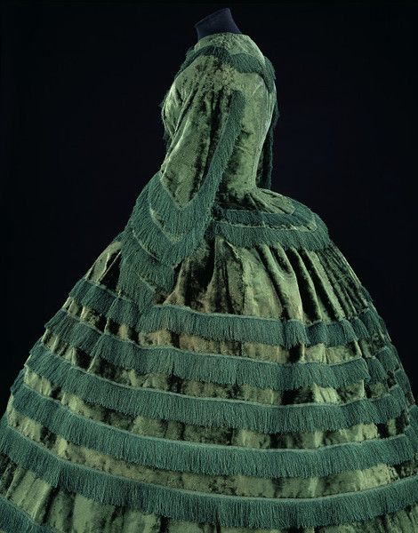 Day dress    Place of origin:  Britain, United Kingdom (made)    Date:  1855-1857 (made)    Artist/Maker:  Unknown (production)    Materials and Techniques:  Silk plush trimmed with silk fringe and braid, bodice lined with silk and whalebone strips