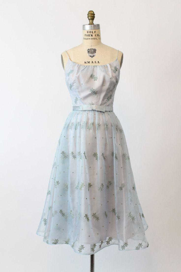 Een schatje van een 1950s jurk! In een pure baby blauwe organza die heeft opgestikte bloemen en getogen polka dots helemaal gedaan. Dunne spaghetti bandjes, afgeronde hals en ingerichte taille. Bijgevoegde satijnen tailleband en boog. Volledige rok. Volledig gevoerd in baby blue satijn. Terug metalen rits en haak en oog.  ♥♥♥ Merk: junior thema new york Grootte op tag: 9 Past als: XS Kleur: baby blauw Materiaal: organza Conditie: Zeer goede Vintage: tiny een paar haken en ogen/pindot gaten…