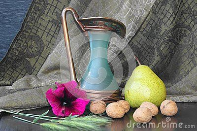 Pears, nuts, spice and petunia on the black background