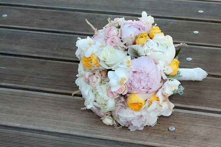 Delicatissimo bouquet di astilbe rosa, peonie, rose inglesi gialle, rose bianche e orchidee phaleanopsis