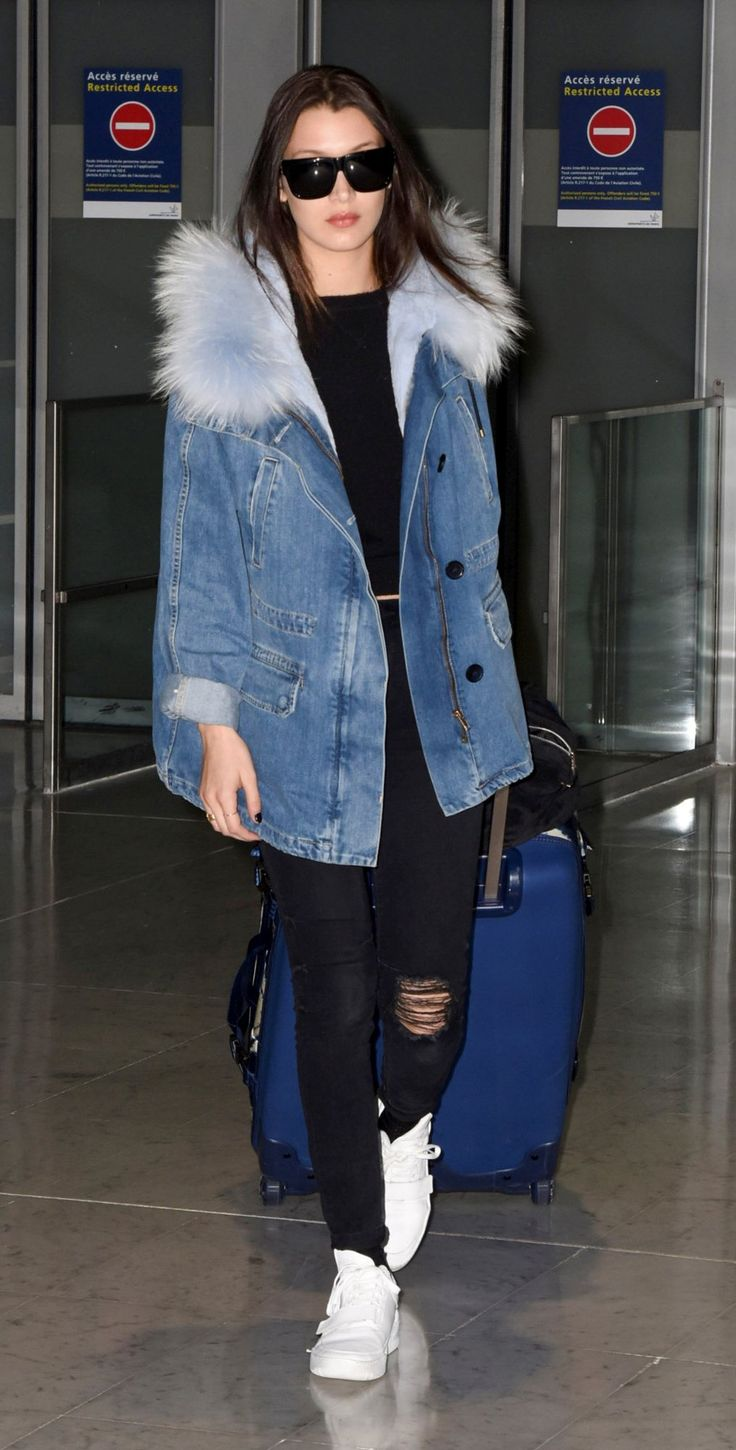 Bella Hadid wears a denim parka by Yves Salomon, black ripped denim, white sneakers, and black sunglasses
