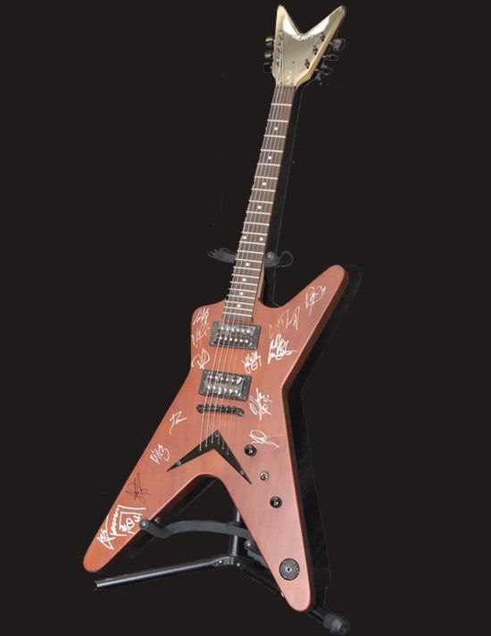 """Dean solid body flying V style electric guitar autographed by Ace Frehely and several others (certified). Includes book """" Ace Frehely No Regrets"""" with Joe Layden and John Ostrosky. Auction online 6/14/2014!"""