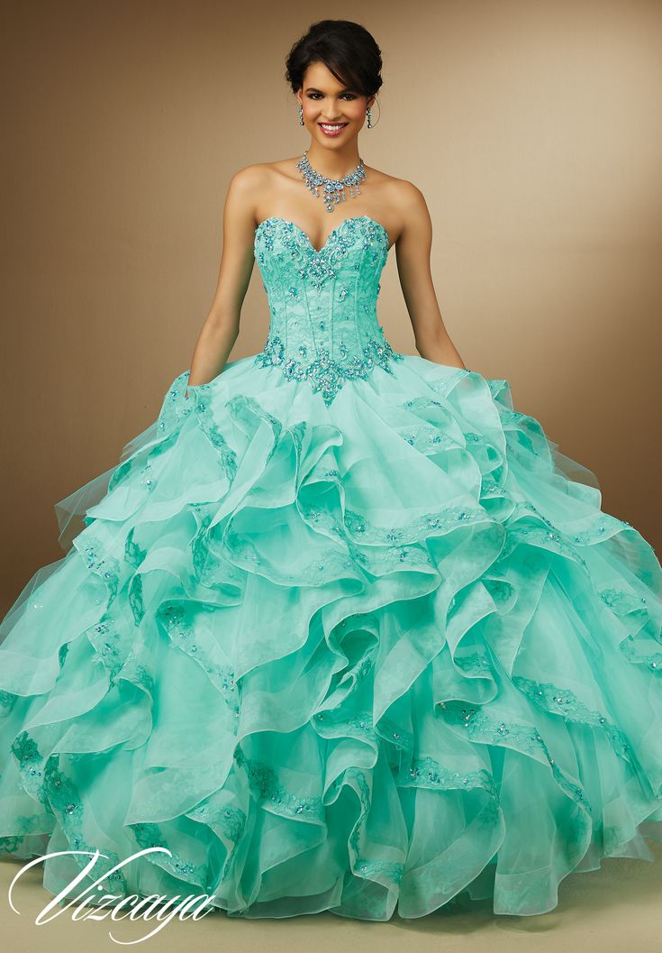 Quinceanera dresses by Vizcaya Embroidery and Beading on Lace with Ruffled Organza Skirt Matching Bolero Jacket. Available in Aqua, Champagne, White