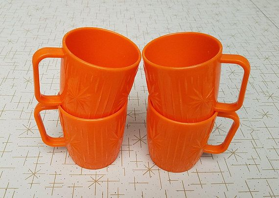 Starburst Mugs Plastic Set of Four Vintage Bright Orange Coffee Cups Mid Century Atomic Sunburst  This is a pretty fantastic set of orange mugs with atomic starbursts on them. The designs are raised, and even the bottoms are decorated. Made of fairly heavy shiny plastic. These are not marked at all; I dont know the manufacturer.  Cups are in good condition. No chips or cracks. All have some normal scuffs and scratches from use and age. There is a white mark on the inside of one. All are…