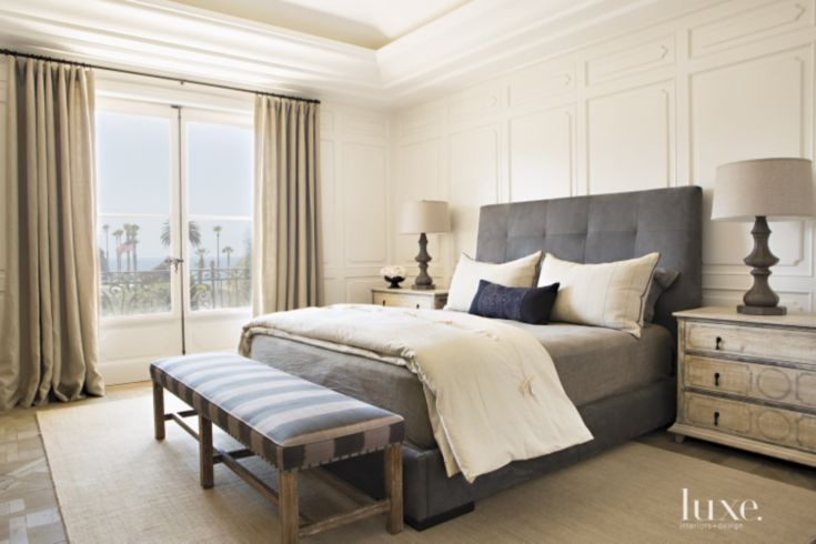 Charcoal-hued suede cloaks the master bedroom's custom bed—dressed with linens from Blue Springs Home—by Wendi Young Design. A bench wears a Jab Anstoetz fabric from Thomas Lavin at Blake House, and the gray weathered-wood lamps are by Arteriors.