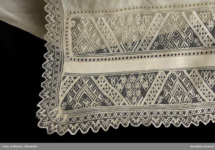 Klutbanden har 2 rader med trädd tyllspets i traditionella sydskånska mönster inom ram av enkel utdragssöm. Banden kantade med uddspets i tyllträdning.