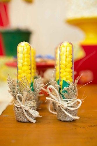 Acomodados em saquinhos de juta, os tubos de plástico recheados com balas amarelas em formato de coração pareciam espigas de milho e serviram como lembrancinha para a festa decorada pela Scrap Encanto