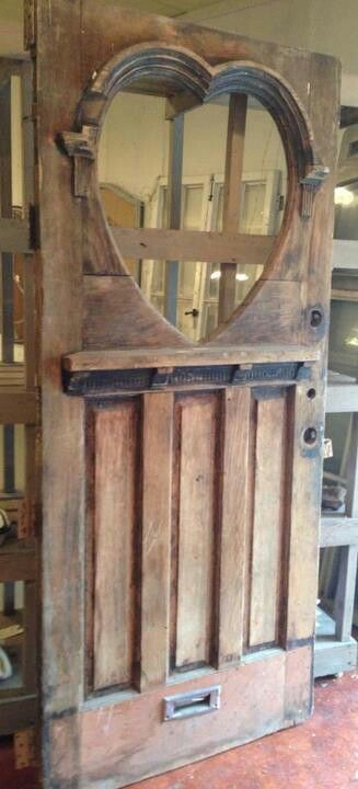 Incredible antique front door with heart-shaped window.