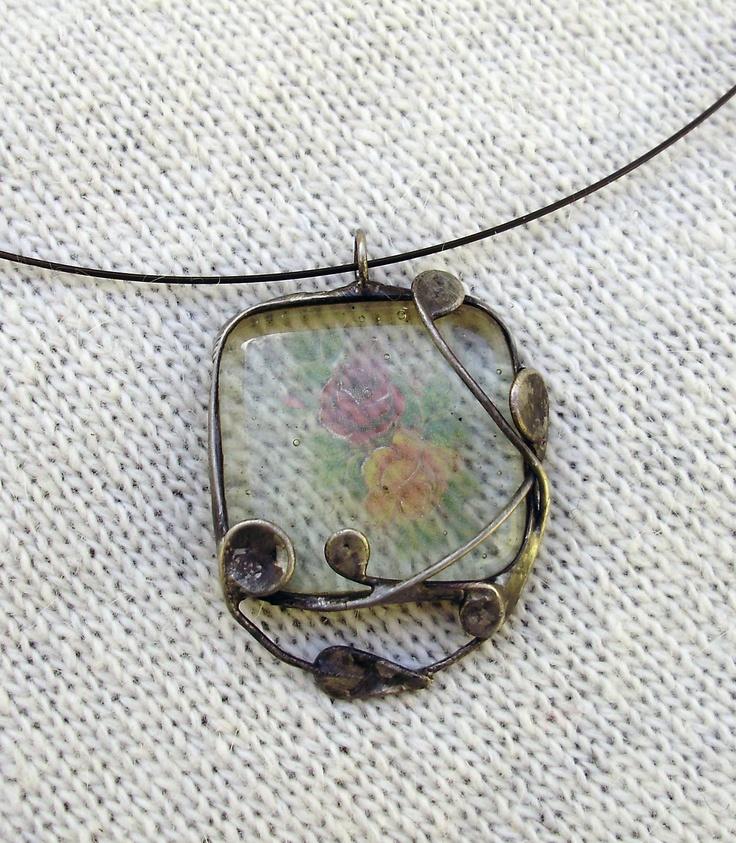 Růžolící Autorský cínovaný náhrdelník se skleněným kabošonem se zapečeným motivem růží. Vyroben z bezolovnatého cínu. Zavěšen na kovové obruči, napatinován, ošetřen antioxidačním prostředkem.