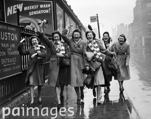 London's April downpour couldn't damp the enthusiasm of these Liverpool girls, garlanded with the colours their team and ringing a hand-bell, as they toured the city before going to Wembley Stadium - FA Cup Final - Arsenal v Liverpool - Wembley Stadium - 29th April 1950
