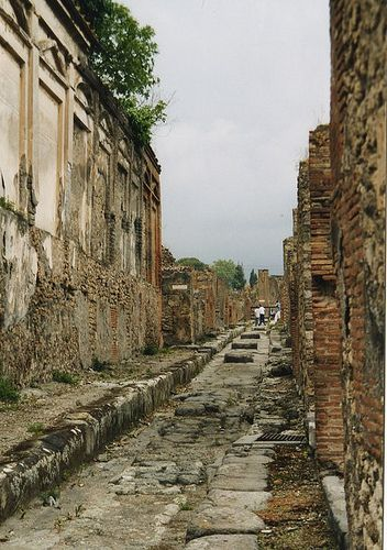 Streets of Pompeii  Downtown Pompeii before the volcano erupted. It was quite the thriving metropolis! Look closely and you will see the raised platforms in the middle of the streets, used for crossing over the rivers of sludge and unmentionable things which flowed freely in this sea-level town. Carts would ride in the trenches formed on either side.