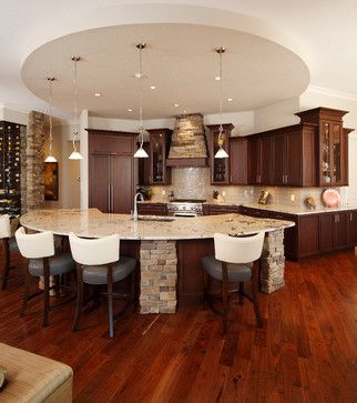 This round kitchen is inviting and functional. We love the use of stone bricks as well as deep stained wood.  www.remodelworks.com