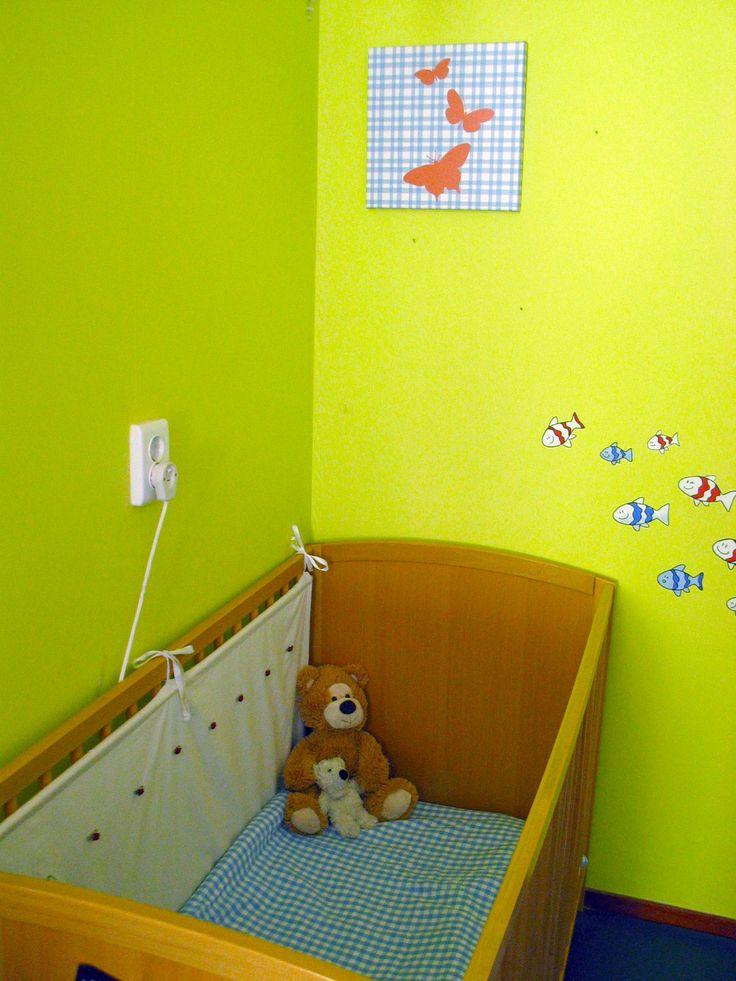 Leuk, een schilderij die past bij het geblokte dekbedje.   De visjes zijn rechtstreeks op de muur geschilderd, wat een heel frivool effect geeft.  In het ledikant een zacht doek met roosjes erop, gemakkelijk zelf te maken: je maakt een tunneltje bovenaan de stof, daar een roede doorheen, de roosjes kun je er zelf opnaaien. Een heel lief effect!