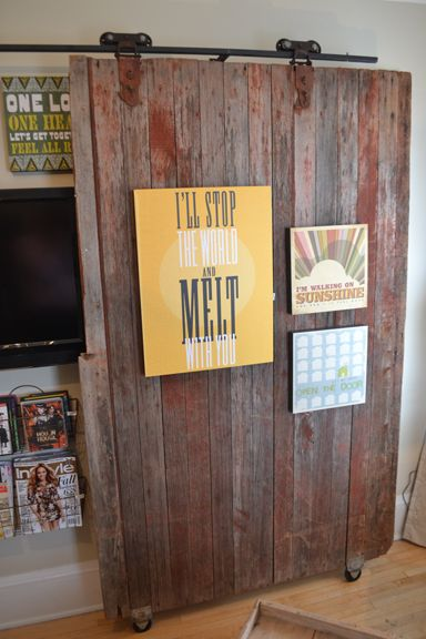 Vintage barn door with musical quotes covers the TV in the media room at the Bachman's Spring Ideas House