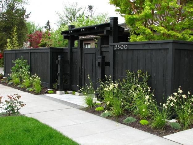 Black fencing serves as simple and effective backdrop for the planting in front.. Could use the grey that the shad is painted in?