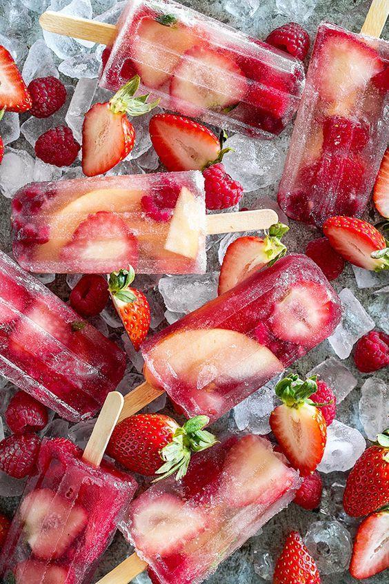 Schneiden Sie Erdbeeren und Pfirsiche in grosse Stücke. Legen Sie die Früchte und einige Himbeeren in eine Schale, und geben Sie ein wenig Puderzucker darüber. Gut mischen. Nun füllen Sie Eislolliformen mit Champagner oder Prosecco, legen die Früchte rein und lassen alles im Eisfach gefrieren.