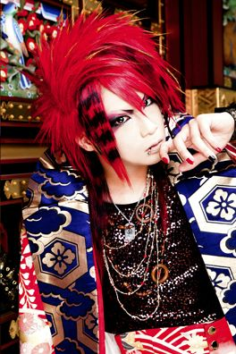 """Sakai Mitsuki (酒井参輝) is the guitarist of Kiryu. He is also in their alter-ego band My Dragon as """"Charity Miki"""". His image color is Red."""
