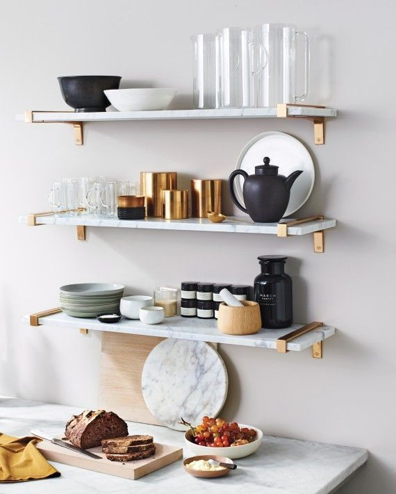 marbled floating shelves, brass brackets, and a muted assortment of natural  textures and matte