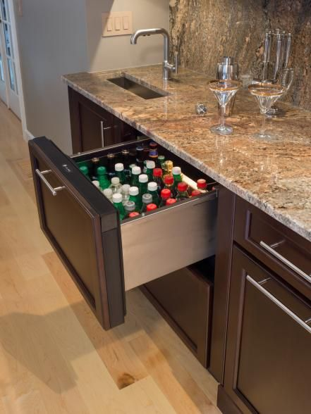 """""""The top refrigerator drawer is perfect for storing cold water, soda, beer — even juice boxes for the kids,"""" Reynolds adds. """"The bottom freezer drawer makes ice and is great for chilling glasses and liquor. Fill the sink up with ice and display the beverages offered to guests for the evening. The far right drawer is handy for bottle openers, napkins and bar utensils for the bartender. Below the drawer is a recycling center pull-out with trash and recycling for the empty bottles. The…"""