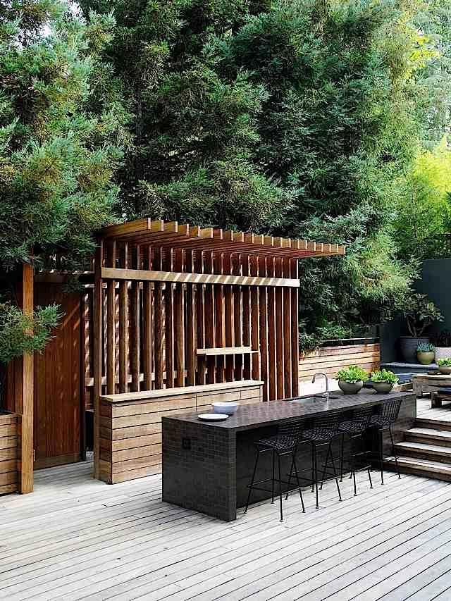 An outdoor bar is a must.  This outdoor kitchen and grill area works awesome for events.  I love the wooden slat canopy.