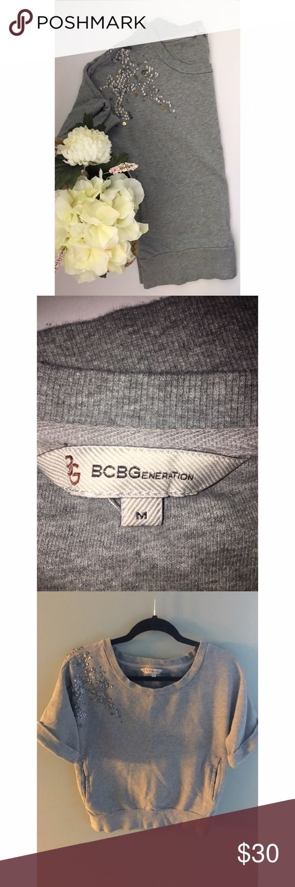 "BCBGenerarion Short Sleeve Embellished Sweatshirt BCBGenerarion Short Sleeve Embellished Sweatshirt  Heather Gray   Embellished spans across front & back of right shoulder.  Short ""rolled"" sleeve   Front pockets gives ""favorite sweats"" feel while embellishments & fit makes this the perfect top for hitting the town.  Pair with black denim & cite heels for a comfy chic look for your next outing.  EUC  Approx Measurements: Bust: 40"" Sleeve:12"" Waist:37"" Length:21.5"" BCBGeneration Tops…"