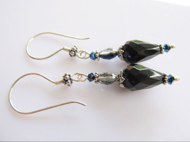 Oorbellen Mirande onyx facet druppel met metttalic blauwe kristal swarovski kraaltjes en kristalglas facet druppeltje. geheel zilver.