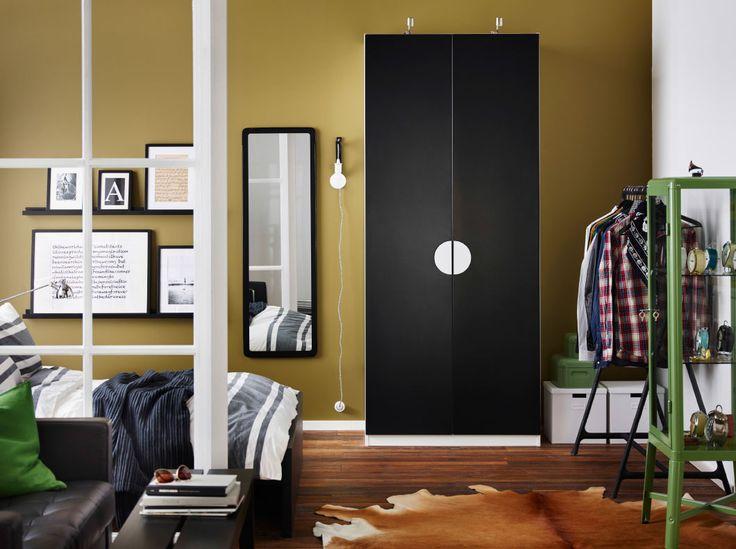 ベッドルームにブラックの扉付きホワイトのワードローブとブラックのベッドとグリーンのガラス扉付きのキャビネット