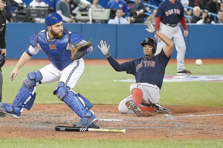 Safe at home: Boston Red Sox shortstop Xander Bogaerts (2) slides safely home to score ahead of the throw to Toronto Blue Jays catcher Russell Martin (55) in the third inning at Rogers Centre on April 8. - © Dan Hamilton-USA TODAY Sports