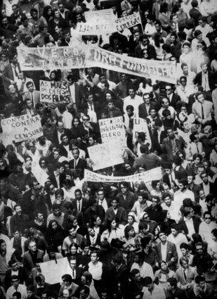 """A ditadura militar no Brasil - Rio de Janeiro, 26/6/1968. Vista de multidão durante a """"Passeata dos 100 mil"""", que reuniu intelectuais, artistas, padres, professores, entre outros, na zona conhecida como Cinelândia, no centro do Rio de Janeiro. A passeata foi uma manifestação de protesto contra a ditadura militar e em consequência do assassinato do estudante secundarista Edson Luís de Lima Souto, em março de 1968, no restaurante Calabouço, no Rio, durante confronto com a PM"""