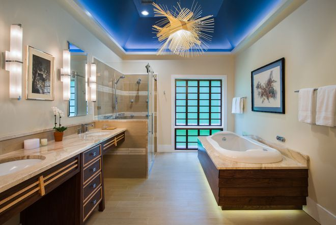 Visual cueing in a bathroom is important for safety, but it becomes even more important for those with vision problems. The lighting at the base of the tub skirt, the detail on the front of the cabinetry and the contrasting colors between cabinetry, countertop and floor all help an individual detect edges and perimeters in the bathroom shown here, allowing for greater confidence in navigating it.