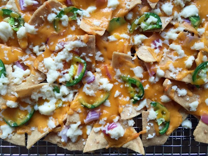 "How to Make Nachos for a Crowd — Alton Brown, ""The key to these nachos is using aluminum foil to make spacers for separating the racks so that maximum meltage is attained. The other thing: fresh oregano. I can't stress that enough."""