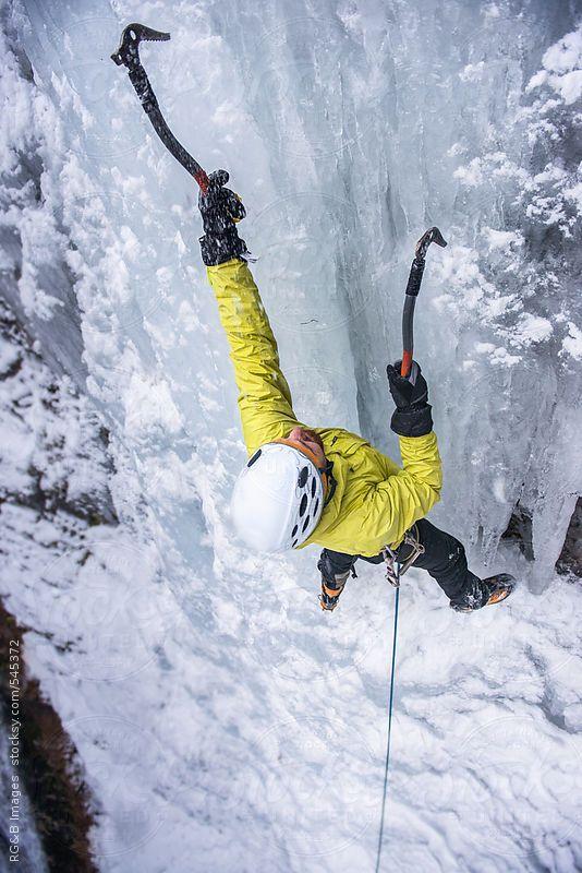 Man ice climbing a frozen and vertical waterfall
