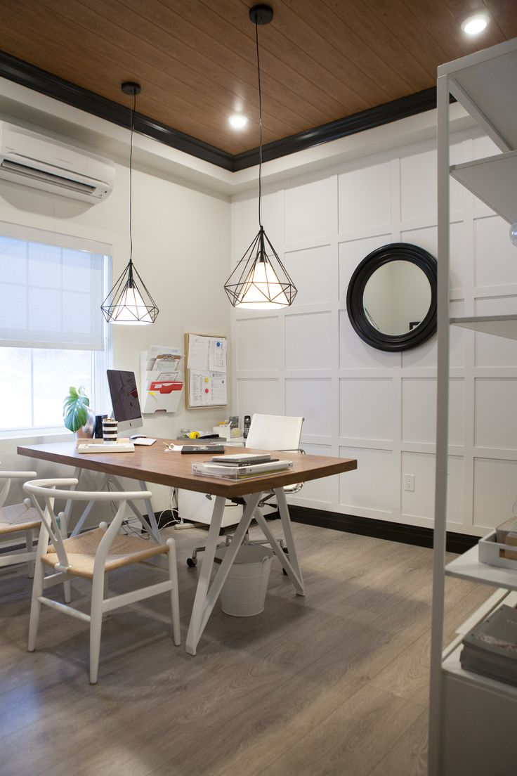 The CEO office pulls the same wood siding from the main area onto it's ceiling framed by black crown molding. A board and batten feature adds drama to the back wall in front of which sits a designer desk and chairs, with designer lighting above.