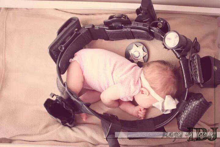 My newborn daughter Reagan in her dad's police duty belt.