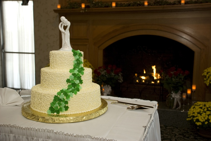 wedding cake with buttercream frosting white on white lace all over cake and then cascading shamrocks down cake. cake topper with our names on arms and irish blessing on skirt of bride.