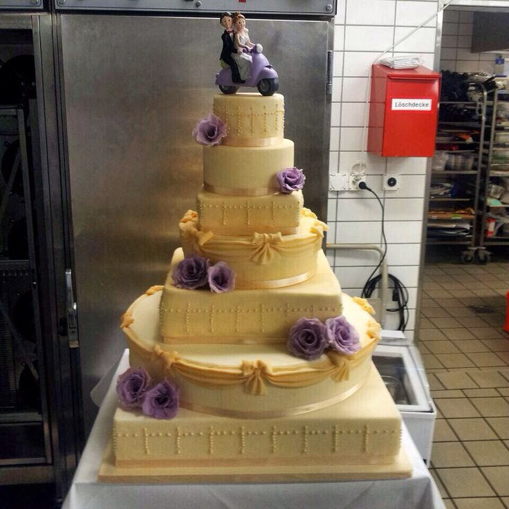 Ivory wedding cake with violet roses and violet Vespa
