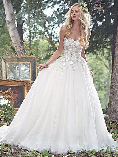 Maggie Sottero - CAMERON, A fitted bodice, glimmering with lace appliqués dotted with Swarovski crystals, cascades into a full tulle skirt in this whimsical ball gown. A romantic sweetheart neckline completes the look. Finished with zipper over inner corset and crystal button closure.