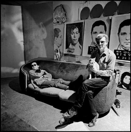 USA. NYC.  Andy WARHOL, painter. - USA. NYC. 1964. Andy WARHOL with the American painter Robert INDIANA (left) in the Warhol studio. - Artist's studio, Cat, INDIANA Robert, Interior, Lying down, Man - 25 to 45 years, Portrait, Seated, Sofa, Sunglasses, Two people, White people