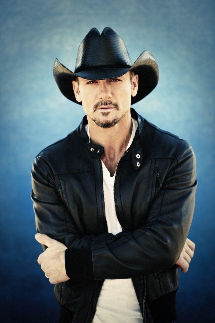 Tim McGraw está llevando un chaqueta negro y una camisa blanco, y un gorra.     El chaqueta cuesta docientos cincuenta euros, el camisa cuesta ciento euros, y el gorra cuesta ciento treinta y seis euros.