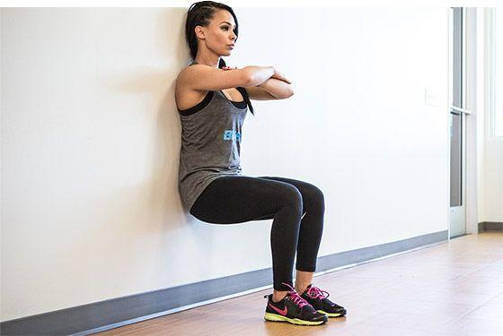 """Cole e alinhe as costas à parede, não é preciso grande pressão, mas o apoio deve ser total e retilíneo. Deslize-se para baixo e um movimento de """"sentar"""" deixando os joelhos flexionados a 90°. Mantenha o olhar no horizonte, coluna ereta, braços cruzados e calcanhar sempre no chão.  Esse exercício trabalha, principalmente, os membros inferiores."""
