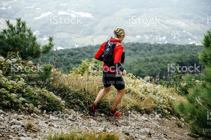 Yalta, Russia - October 5, 2016: male athlete marathon runner running with mountains along trail during Crimea mountain marathon