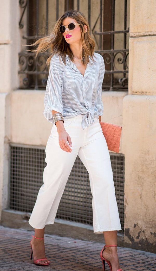 Street style look com camisa listrada e calça branca culotte.