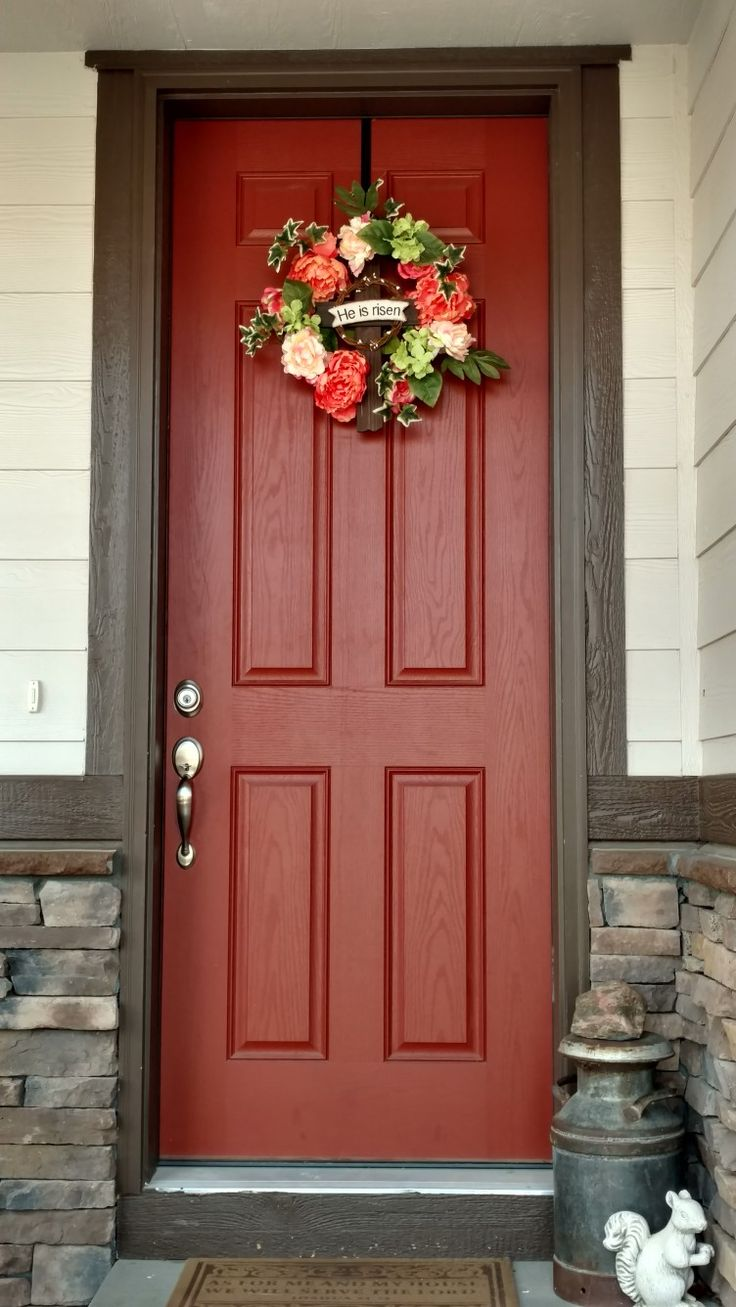 Cream and chocolate brown house with burnt orange door and coral colored spring wreath