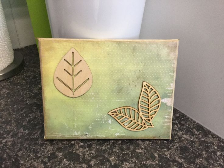 Small canvas with scrapbook paper, wooden embellishments and distress ink around edges.
