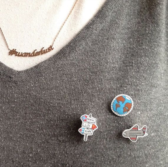 3 super cute handmade pins for travellers.  A plane, an Earth and a road direction.