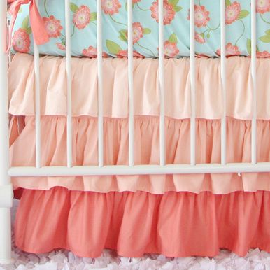 """Caden Lane's coral gradient ruffle crib skirt has cascading ruffles in shades of coral with a 17"""" drop."""
