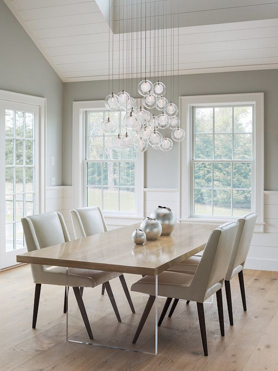Modern dining room boasts gray paint on upper walls and tongue and groove on lower walls alongside a cluster of staggered mini glass globe light pendants illuminating a wood and lucite dining table lined with taupe leather dining chairs.