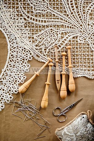 Pillow lace or bobbin lace 'merletto a tombolo' made from 100% linen thread using wooden bobbins (fuselli or piombini), woven using pins on paper designs, Anghiari, Tuscany, Italy