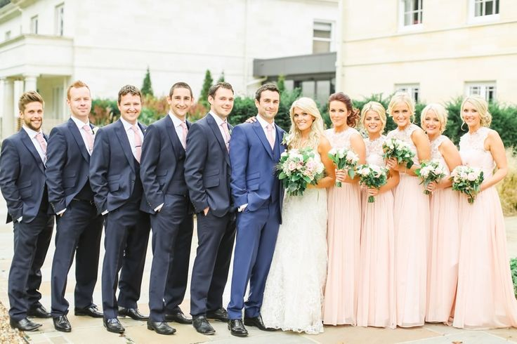 Summer Bridal Party Portrait in peach dresses & Navy Suit s- Image by Belle and Beau Photography - An Ian Stuart 'Sapphire' bridal gown for a classically romantic wedding at Rudding Park in Harrogate with a Dahlia bouquet and pink bridesmaid dresses www.rockmywedding.co.uk