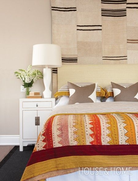 Hang a kilim rug on the wall to extend a headboard and bring more attention to the bed.